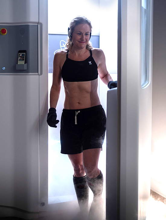 athletic woman exiting cryo chamber after therapy