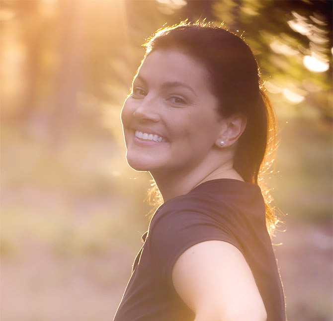 A healthy smiling female client goes for a run in the golden sunlight