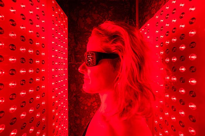 A woman wears protective eyewear as she stands in the red light therapy chamber